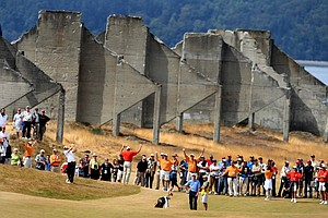 A crowd follows Peter Uihlein and Morgan Hoffmann at No. 18 during quarterfinals of the 110th U.S. Amateur Championship at Chambers Bay in University Place, Wash. In the background are the remains of sorting bins left over from when the course was a gravel mine operation.