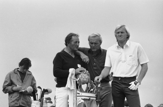 Arnold Palmer, USA (center) seems to be wondering which club Greg Norman of Australia will select during their practice on July 15, 1981 in Sandwich, England for the Open Golf Championship. At left is Norman's Caddie Scottie Gilmour.