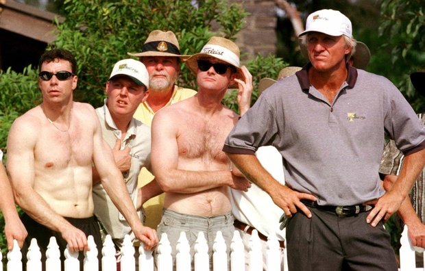 Dressed to combat the searing weather conditions, spectators stand behind International Presidents Cup golfer Greg Norman, right, as they follow the flight of American Lee Janzens' drive during the morning foursomes on the second day of the Presidents Cip at Royal Melbourne Golf Course, Australia Saturday, Dec. 12, 1998.
