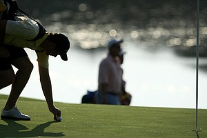 Geogia Tech's Kyle Scott is silhouetted as he marks his ball near the end of play during Tuesday stroke play at the 2011 NCAA Division I Men's Golf Championship.