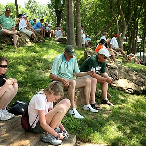 Spectators sit on the hillside at No. 18 during Tuesday stroke play at the 2011 NCAA Division I Men's Golf Championship.
