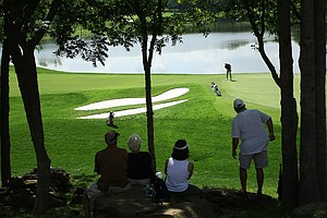 Spectators sit on rocks on the hillside at No. 18 during Tuesday stroke play at the 2011 NCAA Division I Men's Golf Championship.