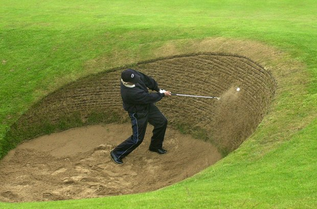 Australia's Greg Norman plays from a bunker alongside the 13th fairway during a practice round for the British Open Golf Championship at Muirfield, Scotland Tuesday, July 16, 2002. The British Open is scheduled to start on Thursday, July 18.