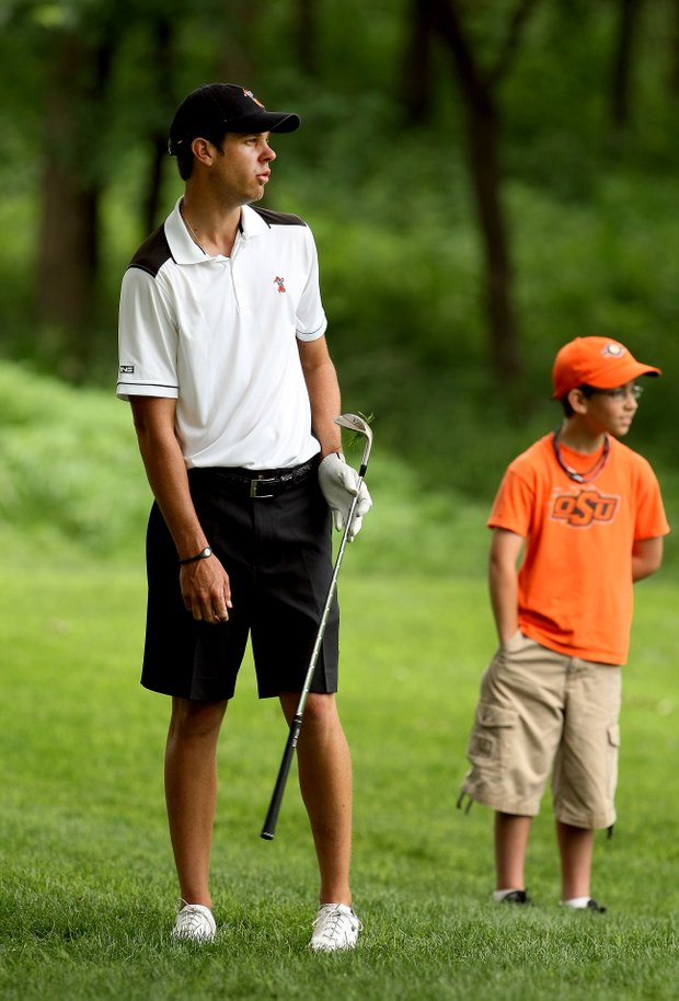 Kevin Tway of Oklahoma State watches his shot roll out at No. 9 as does OSU fan, Jackson White, 10 of Tulsa, Oklahoma.