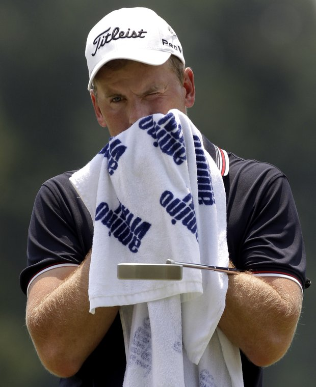 Robert Karlsson, of Sweden, towels off after putting for par on the second hole during the third round of the St. Jude Classic golf tournament Saturday, June 11, 2011, in Memphis, Tenn.