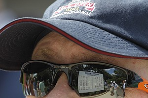 Fans look at practice round starting times in a reflection in the sunglasses of a fan during a practice round for the U.S. Open Championship golf tournament in Bethesda, Md., Tuesday, June 14, 2011.