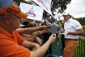 Phil Mickelson signs autographs after a practice round for the U.S. Open Championship golf tournament in Bethesda, Md., Tuesday, June 14, 2011.