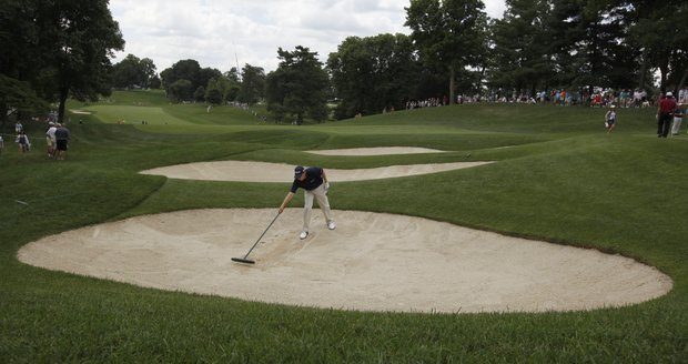 Will Wilcox racks the sand after hitting out of the bunker along the 15th fairway during a practice round for the U.S. Open Championship golf tournament in Bethesda, Md., Tuesday, June 14, 2011.