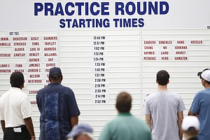 Fans look at the starting board during a practice round for the US Open Championship golf tournament in Bethesda, Md. Monday, June 13, 2011.