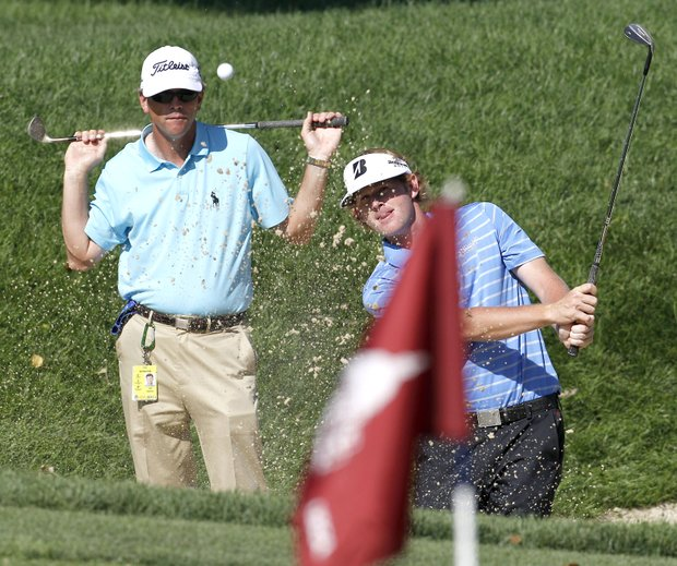 Brandt Snedeker, right, is watched by his swing coach, Todd Anderson, as he hits from a sandtrap on the practice green during a practice round for the U.S. Open Championship golf tournament in Bethesda, Md., Tuesday, June 14, 2011.