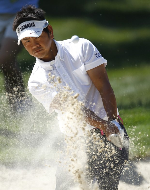 Hiroyuki Fujita, of Japan, hits out of a bunker on the 14th hole during a practice round for the U.S. Open Championship golf tournament in Bethesda, Md., Tuesday, June 14, 2011.