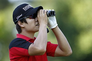 Kim Dohoon of South Korea looks through binoculars during a practice round for the U.S. Open Championship golf tournament in Bethesda, Md., Tuesday, June 14, 2011.
