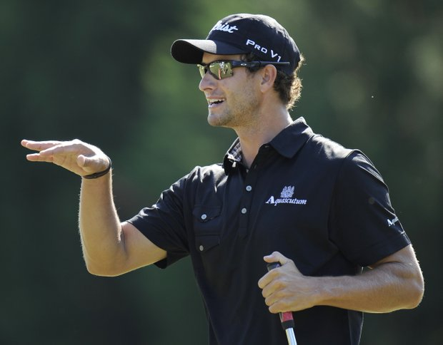 Adam Scott, of Australia, reacts to a putt on the 14th hole during a practice round for the U.S. Open Championship golf tournament in Bethesda, Md., Wednesday, June 15, 2011.