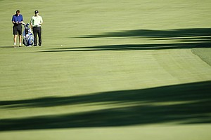 Luke Donald, of England, right, accompanied by his caddie Jon McLaren, waits to hit on the third fairway during a practice round for the U.S. Open Championship golf tournament in Bethesda, Md., Wednesday, June 15, 2011.