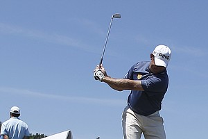 A bird walks past Lee Westwood, of England, as he warms up on the practice tee before a practice round for the U.S. Open Championship golf tournament in Bethesda, Md., Wednesday, June 15, 2011.