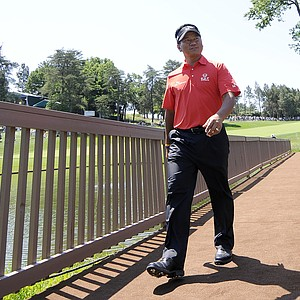 K. J. Choi, of South Korea, walks across the players bridge from the 18th green during a practice round for the U.S. Open Championship golf tournament in Bethesda, Md., Wednesday, June 15, 2011.