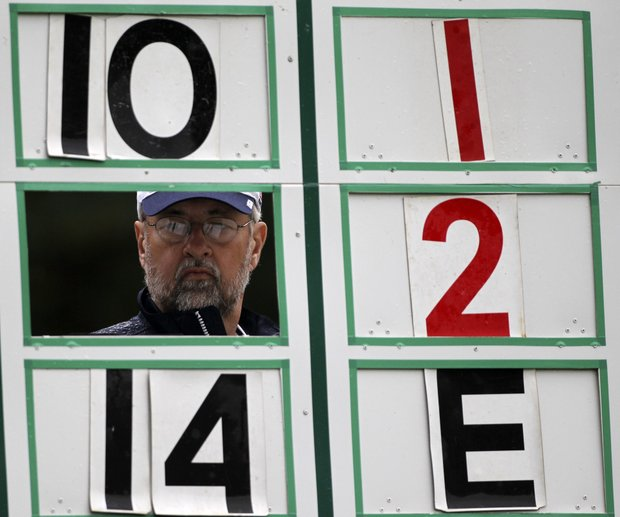 Scorekeeper Clint Siemens looks through the scoreboard along the second hole during the first round of the U.S. Open Championship golf tournament in Bethesda, Md., Thursday, June 16, 2011.