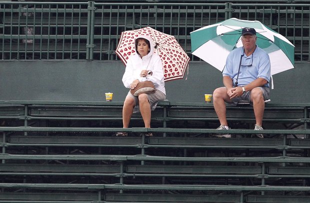 Two golf fans sits under their umbrellas in the near empty grand stands at the 10th hole during the first round of the U.S. Open Championship golf tournament in Bethesda, Md., Thursday, June 16, 2011.