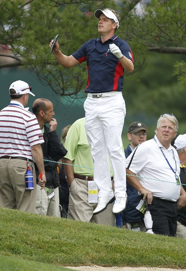 Luke Donald, of England, leaps to see the green from the rough along the 16th fairway during the first round of the U.S. Open Championship golf tournament in Bethesda, Md., Thursday, June 16, 2011.