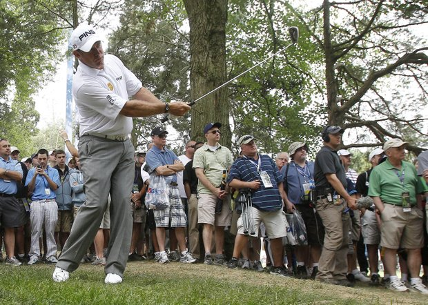 Lee Westwood, of England, watches his shot from the trees along the 18th fairway during the first round of the U.S. Open Championship golf tournament in Bethesda, Md., Thursday, June 16, 2011.