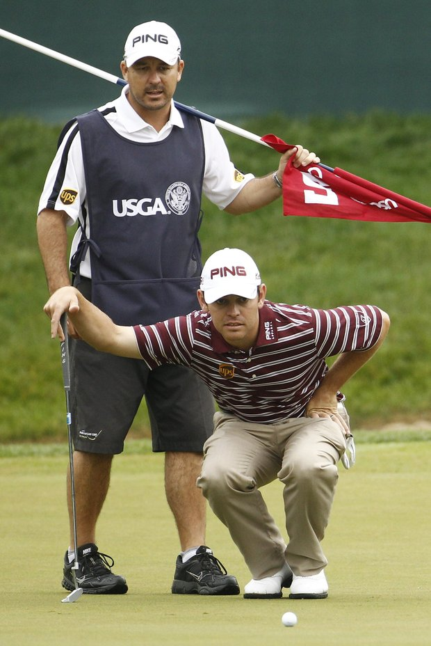 Louis Oosthuizen, right, of South Africa, and his caddie Wynand Stander, look over Oosthuizen's putt on the fifth green during the first round of the U.S. Open Championship golf tournament in Bethesda, Md., Thursday, June 16, 2011.