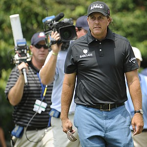 A television crew follows Phil Mickelson down the 10th fairway during the first round of the U.S. Open Championship golf tournament in Bethesda, Md., Thursday, June 16, 2011.