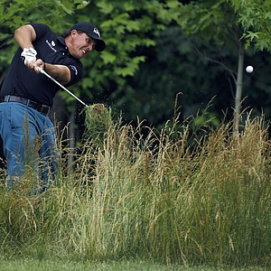 Phil Mickelson hits out of the tall grass along the 14th fairway during the first round of the U.S. Open Championship golf tournament, Thursday, June 16, 2011, in Bethesda, Md.