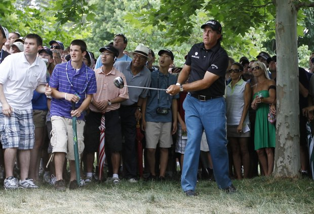 Phil Mickelson watches his shot from the trees along the 16th fairway during the first round of the U.S. Open Championship golf tournament in Bethesda, Md., Thursday, June 16, 2011.