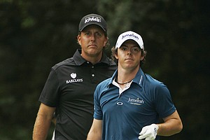 Phil Mickelson, left, looks over Rory McIlroy, of Northern Ireland, shoulder on the 14th fairway during the first round of the U.S. Open Championship golf tournament, Thursday, June 16, 2011, in Bethesda, Md.
