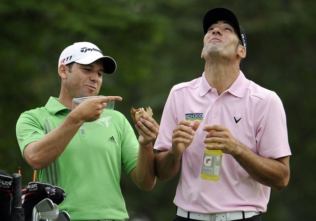 Sergio Garcia, left, of Spain, points to a bite that Alvaro Quiros, also of Spain, took out of his sandwich during the first round of the U.S. Open Championship golf tournament in Bethesda, Md., Thursday, June 16, 2011.