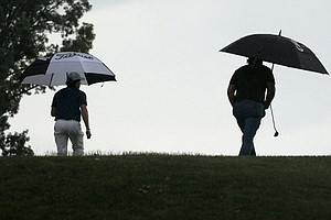Rory McIlroy, of Northern Ireland, left, and Phil Mickelson, walk over the hill to the ninth green during the first round of the U.S. Open Championship golf tournament in Bethesda, Md., Thursday, June 16, 2011.