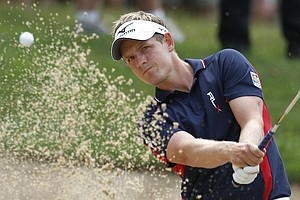 Luke Donald, of England, watches his bunker shot to the 17th green during the first round of the U.S. Open Championship golf tournament in Bethesda, Md., Thursday, June 16, 2011.