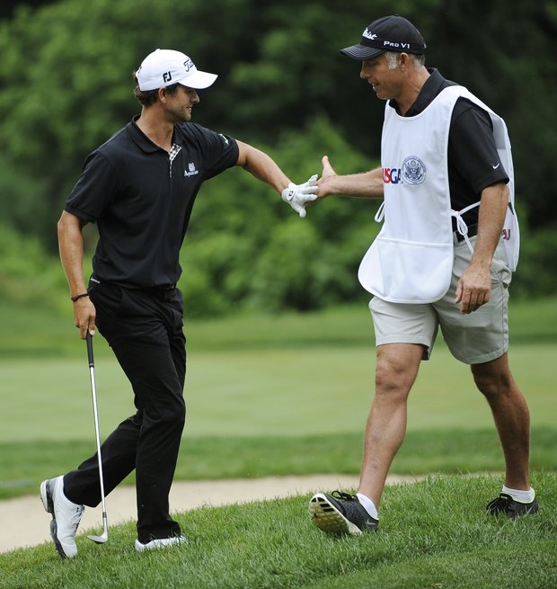 Adam Scott, of Australia, left, celebrates his shot to the 13th green with his caddie Steve Williams, during the first round of the U.S. Open Championship golf tournament in Bethesda, Md., Thursday, June 16, 2011.