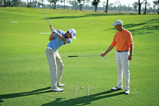 "You'll need a friend to perform this drill, but it's another good one to keep players from ""flipping"" their hands at impact. Love grips a club by the hosel and points the grip at Kirk's hands. The grip is only a couple of inches from Kirk's hands. If Kirk swings too far in-to-out through impact, or turns his hands too much, his hands will hit the grip. Kirk must keep his hands ""dead""and use his body to deliver the club through impact to avoid hitting the grip with his hands. ""He just instinctively uses less hands and swings a little more down the line than in-to-out,"" Love said."