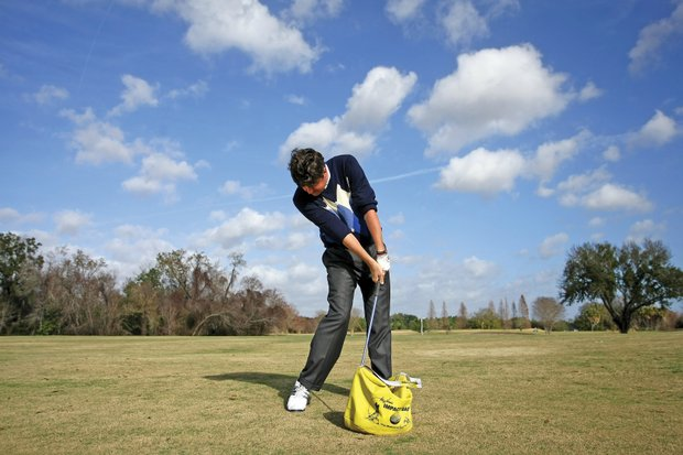 """Smith uses an impact bag to improve his point of contact, and it also helps his backswing by forcing him to focus on using his core to turn. """"It gets me in a really strong position at the top,"""" Smith said. """"When you're going to hit that bag, you have to be in such a strong position at the top of the swing to be able to level a blow."""" The impact bag also keeps Smith from standing up and spinning out in the downswing. """"Your hands are ahead of the ball, and your head stays back,"""" Smith said. """"It almost feels like you're keeping your back to the target while you move into the ball, like you're pushing against someone who's pushing against your back, as your hands move down."""""""