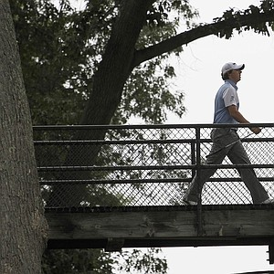 Rory McIlroy, of Northern Ireland, walks across the players bridge at the ninth hole during the third round of the U.S. Open Championship golf tournament in Bethesda, Md., Saturday, June 18, 2011.