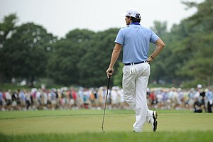 Rory McIlroy, of Northern Ireland, waits for his turn to putt on the fourth green during the final round of the U.S. Open Championship golf tournament in Bethesda, Md., Sunday, June 19, 2011.