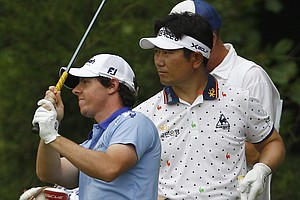 Y. E. Yang, of South Korea, right, looks on as Rory McIlroy, of Northern Ireland, tees off on the sixth hole during the final round of the U.S. Open Championship golf tournament in Bethesda, Md., Sunday, June 19, 2011.