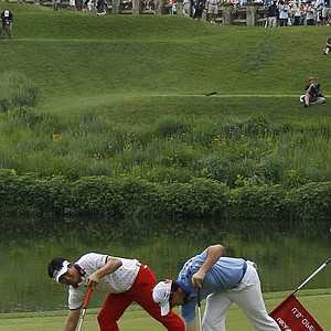 Rory McIlroy, of Northern Ireland, right, and Y. E. Yang, of South Korea, mark their balls on the 10th green during the final round of the U.S. Open Championship golf tournament in Bethesda, Md., Sunday, June 19, 2011.
