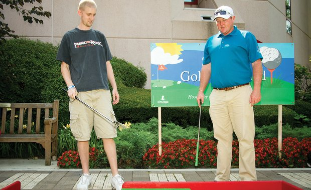 St. Jude patient John (left) and Jarrod Lyle play mini-golf at Golf-A-Round.