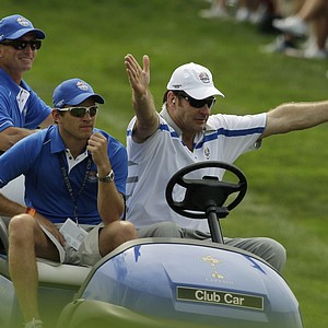 Europe team captain Nick Faldo signals to spectators to make way for his golf cart at the first hole during their four-ball match at the Ryder Cup golf tournament at the Valhalla Golf Club, in Louisville, Ky., Friday, Sept. 19, 2008. Nick's son, Matthew Faldo, is seated at left.