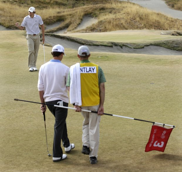 As Patrick Cantlay and his caddie look on, Peter Uihlein pumps his fist after sinking a putt on the third hole during a semifinal match of the U.S. Amateur golf tournament, Saturday, Aug. 28, 2010, at Chambers Bay in University Place, Wash. Uihlein will face David Chung in the final match on Sunday.