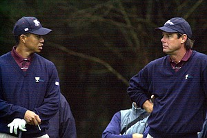 Tiger Woods, left, and Paul Azinger, right, talk before teeing off on the second hole of a practice round for the Presidents Cup at the Robert Trent Jones Golf Club in Gainesville, Va., Tuesday, Oct. 17, 2000.