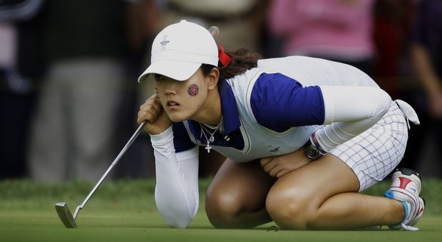 Team USA's Michelle Wie lines up a putt on the eighth hole during a four-ball match at the Solheim Cup golf tournament Saturday, Aug. 22, 2009, at Rich Harvest Farms in Sugar Grove, Ill.