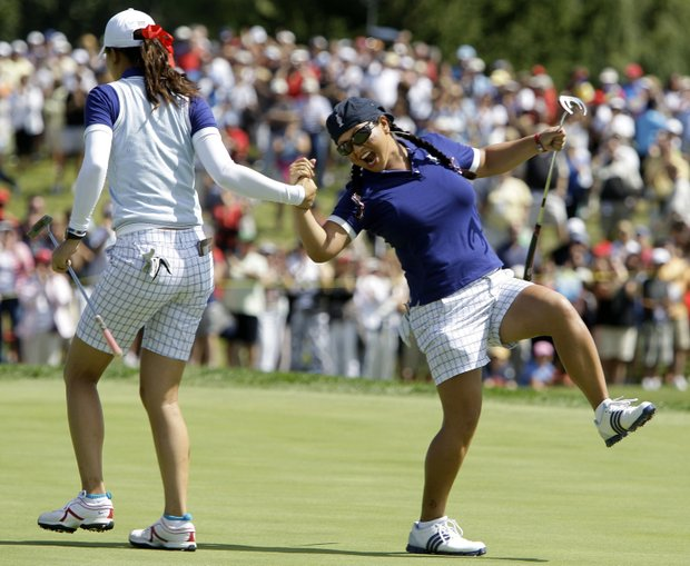 Team USA's Michelle Wie, left, is congratulated by Christina Kim after making a birdie putt on the 11th hole during a four-ball match at the Solheim Cup golf tournament Saturday, Aug. 22, 2009, at Rich Harvest Farms in Sugar Grove, Ill.