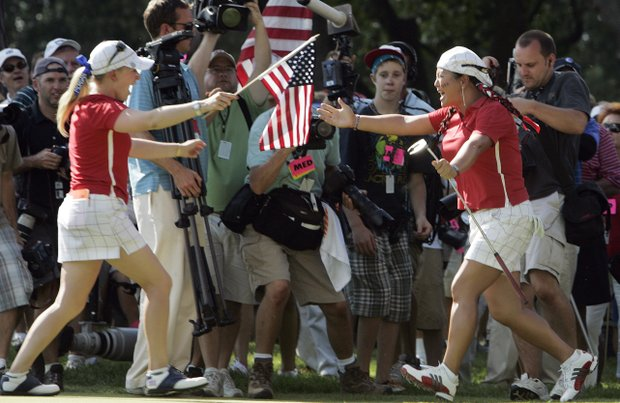 Team USA's Morgan Pressel, left, runs to hug Christina Kim on the 18th hole after their singles match at the Solheim Cup golf tournament Sunday, Aug. 23, 2009, at Rich Harvest Farms in Sugar Grove, Ill. The USA team won 16-12 to retain the cup.