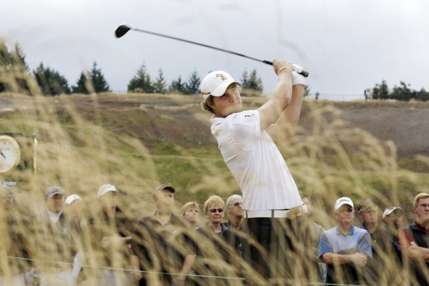 Peter Uihlein is seen through tall grass as he tees off the 10th hole in the quarterfinal round of the U.S. Amateur golf tournament, Friday, Aug. 27, 2010, at Chambers Bay in University Place, Wash.