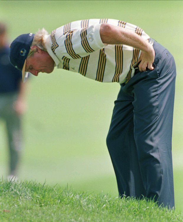 Presidents Cup International team member Greg Norman dejectedly looks over a ball in the rough near the 14th green during first round matches at the Robert Trent Jones Golf Club in Gainesville, Va., on Friday, Sept. 13, 1996. Norman and teammate Robert Allenby lost their match to Fred Couples and Davis Love III.
