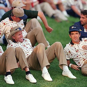 The International team of Mark McNulty, left, Greg Norman, David Frost, right, and Frank Noblio, top right, watch play on the 18th green during the fourth round of the President's Cup Golf torunament at the Robert Trent Jones Golf Club in Gainesville, Va., on Saturday, Sept. 14, 1996. The team made up several points to go into Sunday's round 10 1/2 to 9 1/2 points.