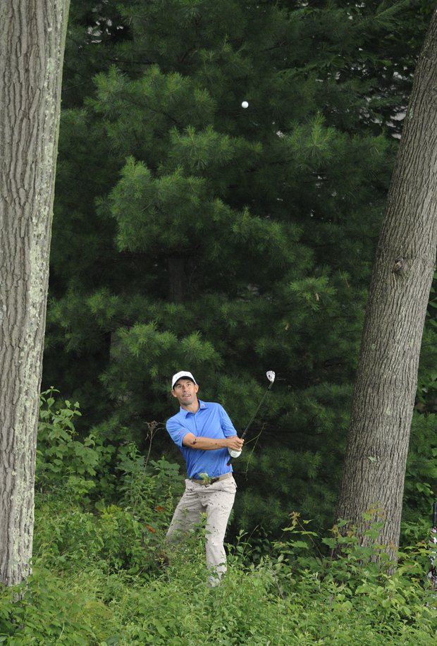 Padraig Harrington, or Ireland, hits out of the trees on the 15th hole during the first round of the Travelers Championship golf tournament in Cromwell, Conn., on Thursday, June 23, 2011.